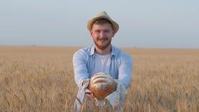 El cultivador feliz del grano del granjero, el hombre joven en sombrero de paja y la camisa azul le da el pan recientemente cocid almacen de metraje de vídeo