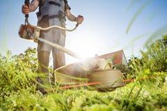 El cultivar un huerto con un brushcutter Imágenes de archivo libres de regalías