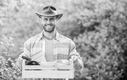 El cultivar un huerto del hombre caja de madera del control atractivo del granjero con la maceta Trabajador de granja de Eco D?a  imagenes de archivo