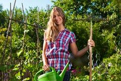 El cultivar un huerto en el verano - mujer con el crisol y el gra del agua fotografía de archivo