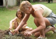 El cultivar un huerto mayor de la mujer y del niño Fotografía de archivo libre de regalías