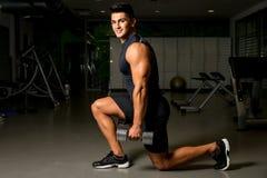 El culturismo de la postura del entrenamiento del hombre ejercita el entrenamiento del peso imagen de archivo