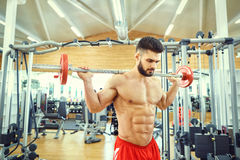 El culturista con un barbell de la barra hace ejercicios en el gimnasio Imagen de archivo
