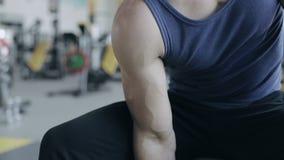 El culturista del hombre ejecuta ejercicio con pesas de gimnasia en gimnasio Ninguna cara metrajes