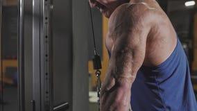 El culturista en tren del gimnasio arma los músculos del tríceps usando la máquina del cable para la masa del cuerpo almacen de metraje de vídeo