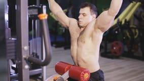 El culturista está trabajando en sus músculos traseros con la máquina del lat en gimnasio almacen de metraje de vídeo