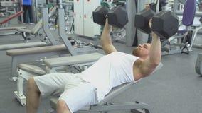 el culturista hace la prensa de banco usando pesas de gimnasia en el gimnasio Hombre muscular que ejercita en el gimnasio almacen de video