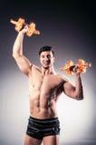 El culturista rasgado muscular con pesas de gimnasia ardientes fotografía de archivo libre de regalías