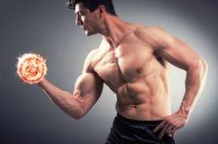 El culturista rasgado muscular con pesas de gimnasia ardientes imágenes de archivo libres de regalías