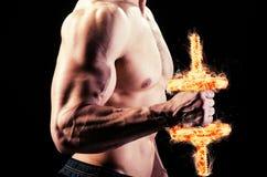 El culturista rasgado muscular con pesas de gimnasia ardientes Foto de archivo