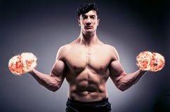 El culturista rasgado muscular con pesas de gimnasia ardientes foto de archivo libre de regalías