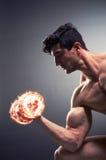 El culturista rasgado muscular con pesas de gimnasia ardientes imagen de archivo