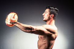 El culturista rasgado muscular con pesas de gimnasia ardientes fotos de archivo libres de regalías