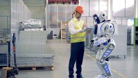El cyborg de la fábrica está consiguiendo instrucciones de un ingeniero de sexo masculino almacen de video