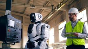 El Cyborg está actuando el equipo de la fábrica bajo control del trabajador almacen de metraje de vídeo