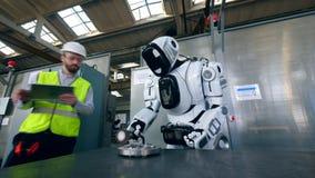 El Cyborg está procesando el metal con un trabajador que se coloca cerca almacen de metraje de vídeo