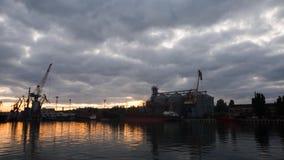 El día al timelapse de la noche del horizonte épico y de la flotación se nubla sobre puerto con las grúas y el terminal grande de metrajes