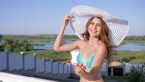 El día de fiesta costoso, la mujer rica feliz en el sombrero y el bañador se está basando sobre el chalet del verano metrajes
