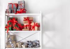 El día de fiesta presenta, las cajas de regalo en los estantes blancos en el fondo de la pared Fotos de archivo