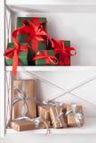 El día de fiesta presenta, las cajas de regalo en los estantes blancos en el fondo de la pared Foto de archivo libre de regalías