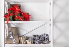 El día de fiesta presenta, las cajas de regalo en los estantes blancos en el fondo de la pared Fotografía de archivo libre de regalías