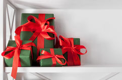 El día de fiesta presenta, las cajas de regalo en los estantes blancos en el fondo de la pared Imagen de archivo