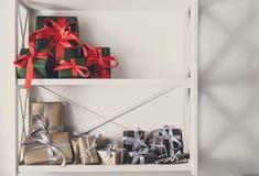 El día de fiesta presenta, las cajas de regalo en los estantes blancos en el fondo de la pared Foto de archivo
