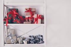 El día de fiesta presenta, las cajas de regalo en los estantes blancos en el fondo de la pared Imágenes de archivo libres de regalías