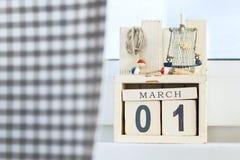 El día de la mujer internacional primero de calendario de madera de los cubos de marzo con las decoraciones de la playa Imagenes de archivo