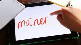 El día de madres feliz, mano escribe el texto en la tableta