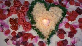 El día de San Valentín de la sorpresa con la flor de la decoración, subió los pétalos y cantidad ardiente de la vela almacen de video