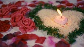 El día de San Valentín de la sorpresa con la flor de la decoración, subió los pétalos y cantidad ardiente de la vela almacen de metraje de vídeo