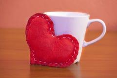 El día de tarjeta del día de San Valentín - corazón rojo y una taza de café Fotografía de archivo libre de regalías
