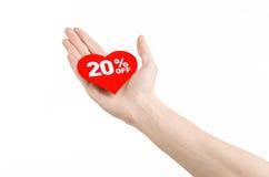 El día de tarjeta del día de San Valentín descuenta tema: Dé sostener una tarjeta bajo la forma de corazón rojo con un descuento  Fotos de archivo