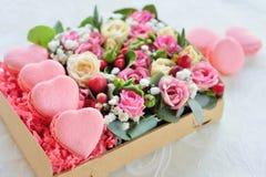 El día de tarjeta del día de San Valentín en forma de corazón de los macarrones franceses, la caja con el flowe Foto de archivo