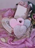 El día de tarjeta del día de San Valentín en las sombras del rosa - corazones en bolso de la malla Imagen de archivo