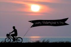 El día de tarjeta del día de San Valentín feliz, bici del hombre de la silueta en el cielo crepuscular de la puesta del sol Fotos de archivo libres de regalías