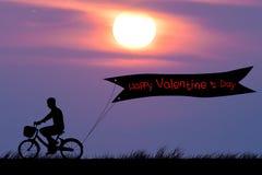 El día de tarjeta del día de San Valentín feliz, bici del hombre de la silueta en el cielo crepuscular de la puesta del sol Imagen de archivo libre de regalías