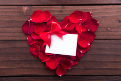 El día de tarjeta del día de San Valentín: La tarjeta de papel vacía blanca, las cintas y el amor rojo formaron los pétalos color Foto de archivo libre de regalías