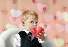 El día de tarjeta del día de San Valentín - niño lindo con el corazón rojo en manos. Imagen de archivo