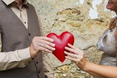El día de tarjeta del día de San Valentín: pares que llevan a cabo el corazón rojo en sus manos Fotografía de archivo libre de regalías
