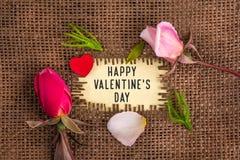El día de tarjeta del día de San Valentín feliz escrito en agujero en la arpillera fotos de archivo