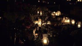 El Día de Todos los Santos Velas que queman en sepulcros en el cementerio en la noche Enfoque hacia fuera 4K metrajes