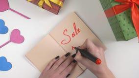 El día del ` s de la tarjeta del día de San Valentín, ejemplo, mano del ` s de la mujer escribe en un cuaderno del marrón oscuro,