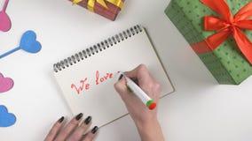 El día del ` s de la tarjeta del día de San Valentín, ejemplo, mano del ` s de la mujer escribe en un cuaderno, nosotros le ama m