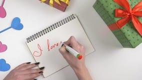 El día del ` s de la tarjeta del día de San Valentín, ejemplo, mano del ` s de la mujer escribe en un cuaderno, te amo mamá 60 fp