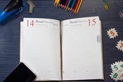 El día diario del ` s de la tarjeta del día de San Valentín del registro en una tabla con los accesorios de la oficina Fotografía de archivo libre de regalías
