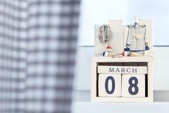 El día ocho de la mujer internacional de calendario de madera de los cubos de marzo con las decoraciones de la playa Foto de archivo