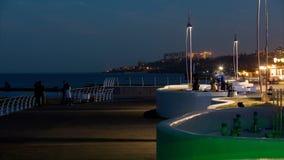 El día se substituye en la gente de la noche está caminando en una playa pública Dolphinarium de la falta de definición en la ori metrajes