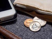 El dólar de EE. UU. acuña colocado fuera de la cartera con smartphone Imagen de archivo